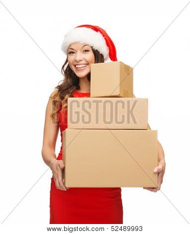 christmas, x-mas, winter, happiness concept - smiling woman in santa helper hat with many parcel boxes