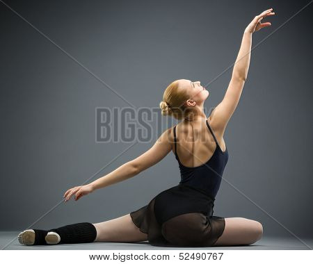Backview of dancing on the floor ballerina with hands up, isolated on grey. Concept of elegant art and sportive hobby