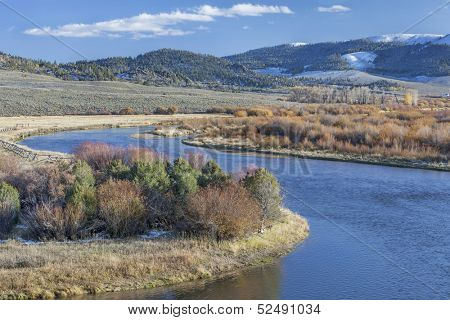 meanders of North Platte River above North Gate Canyon near Cowdrey, Colorado, in a fall scenery with some snow in surrounding mountains