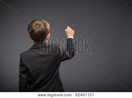 Backview of boy writing, on grey background. Concept of leadership and success
