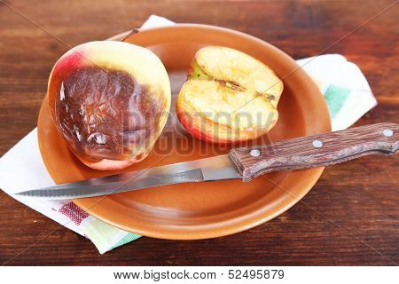 Rotten apples on plate on table