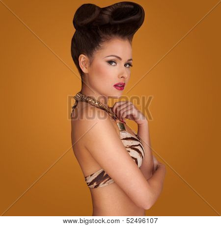 Beautiful pin up girl with a glamorous swept up hairdo wearing gold jewellery posing in an animal print bikinin against a brown studio background