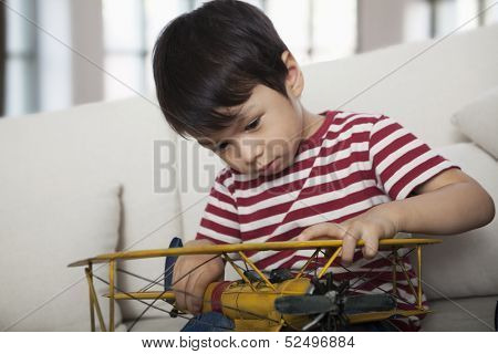 Little boy looking down and holding a model airplane