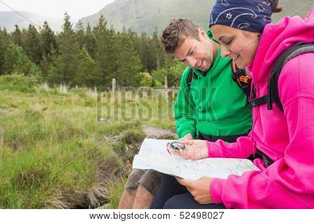 Couple sitting on a rock resting during hike using map and compass in the countryside