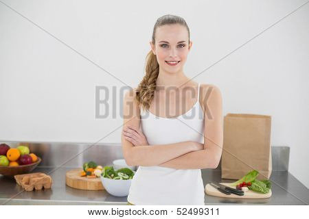 Pretty smiling woman standing cross-armed in bright kitchen