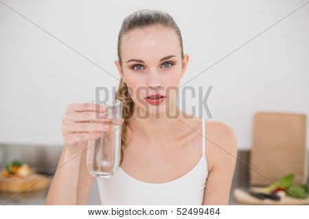 Serious young woman holding glass of water in the kitchen at home