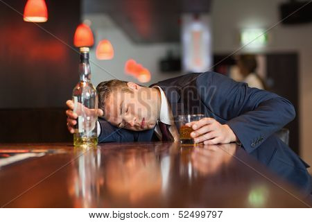 Unmoving businessman holding whiskey glass lying on a counter in a classy bar