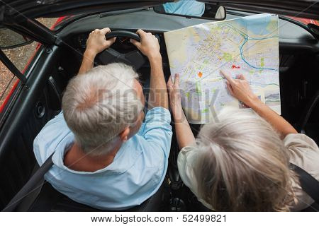 Overhead view of mature couple reading map in classy convertible