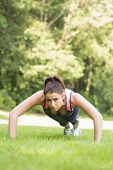 Focused fit woman doing plank position on the grass looking at camera