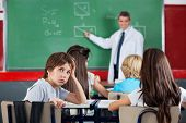 picture of schoolboys  - Portrait of young schoolboy leaning at desk with teacher teaching in background - JPG