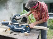 picture of workbench  - Closeup of mature man sawing lumber with sliding compound miter saw outdoors sawdust flying around - JPG