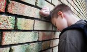 stock photo of sob  - upset boy against a wall - JPG