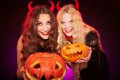 stock photo of antichrist  - Portrait of two horned females showing carved Halloween pumpkins and looking at camera - JPG