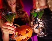 stock photo of repentance  - Photo of carved Halloween pumpkin and cocktails with scorpions held by females - JPG