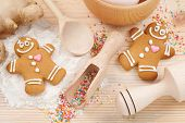 stock photo of ginger bread  - funny gingerbread men flour rolling pin spoon and ginger on kitchen table - JPG