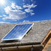 stock photo of shingle  - Old roof with wooden shingles and solar panel with reflection of blue sky - JPG
