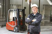 foto of forklift  - young smiling warehouse worker driver in uniform in front of forklift stacker loader - JPG