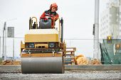 stock photo of vibrator  - Light vibration roller compactor at urban road construction and repairing asphalt pavement works - JPG