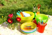 stock photo of table manners  - A table with bright multicolor summer picnic plastic accessories plates and dishes napkins bottles and flowers - JPG