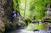 foto of climbing wall  - Woman climbing on a mountain wall over a river in a canyon - JPG