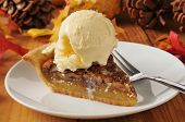 stock photo of pecan  - a slice of pecan pie with vanilla ice cream on a colorful holiday table - JPG