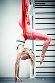 foto of upside  - Young woman making antigravity yoga exercises - JPG