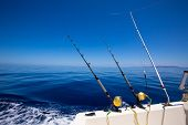 stock photo of troll  - Ibiza fishing boat trolling with rods and reels in blue Mediterranean sea Balearic - JPG