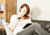 foto of recliner  - Pretty young redhead woman reading a book reclining on a black leather sofa with a glass or red wine in her hand and a smile of contentment on her face - JPG