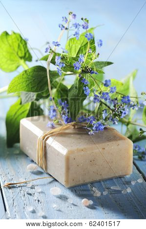 natural soap with little flowers on a blue wooden table