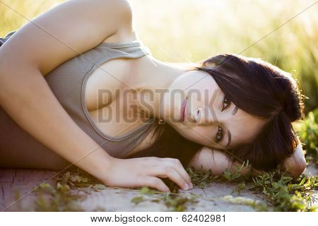 Young beautiful girl laying in nature, under the sun.