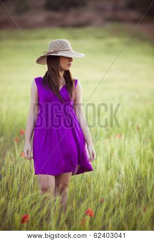 Young girl on field hiding her eyes below her hat.