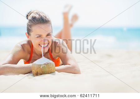 Young Woman Laying On Beach And Drinking Coconut Milk