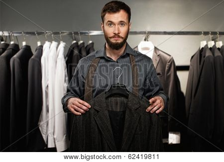 Handsome man with beard choosing jacket in a shop