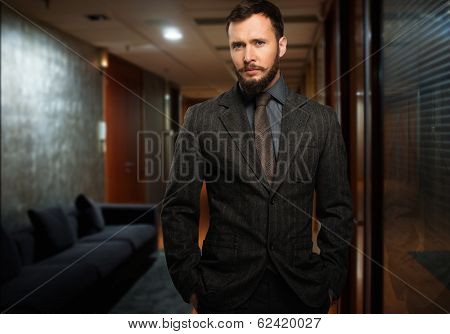 Handsome well-dressed man with beard in a hallway