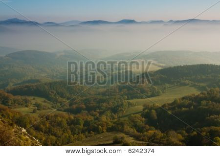 Green Valley With Mountains In Fog