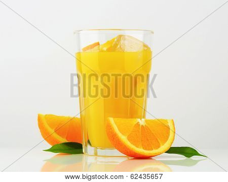 glass of orange juice, decorated with fresh oranges and green leaves