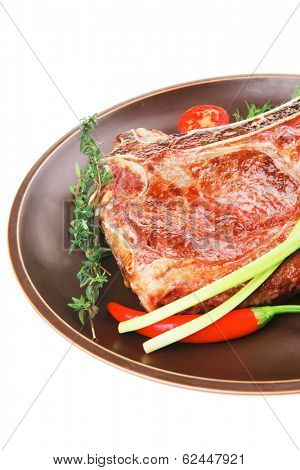 savory : grilled spare rib on dark dish with thyme pepper and tomato isolated over white background