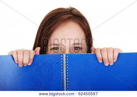 Beautiful woman behing blue workbook. Over white background.