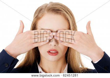 Beautiful business woman covering her eyes. Isolated on white.
