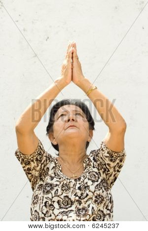 Elderly Woman Raising Hands To Worship
