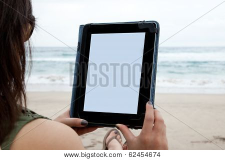Woman using tablet device while on a beach