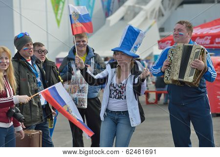 SOCHI, RUSSIA - FEBRUARY 12, 2014: Russian fans with national flags sing the song in Olympic Park during XXII Winter Olympics. Russia hosts the second Olympics in history