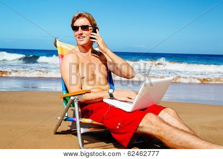 Young Attractive Casual Businessman Entrepreneur Relaxing at the Beach with Laptop Computer Talking on Cell Phone