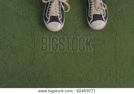 Black sneakers on a green welcome mat
