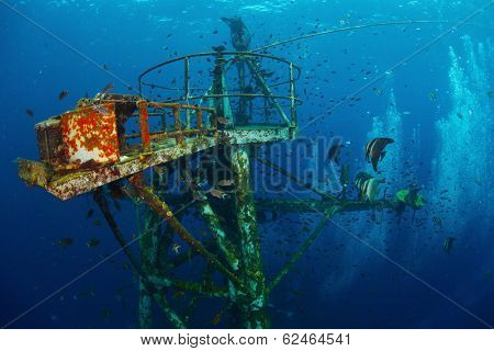 Underwater shot of top of HTMS Chang LST-712 (formerly USS Lincoln County (LST-898)) with bubbles and schooll of fish. Thailand