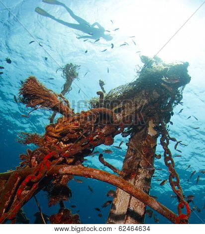 Underwater shot of the ship wreck with snorkeler's silhouette on the surface