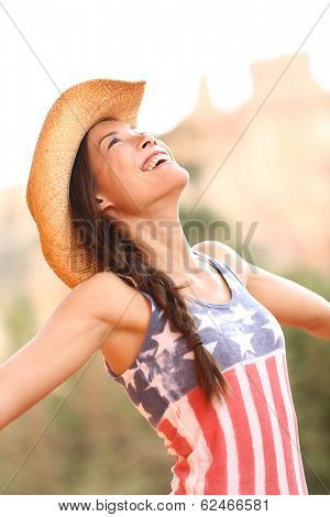 American cowgirl woman free and happy wearing cowboy hat outdoors in countryside. Cheerful elated joyful woman smiling enjoying freedom. Beautiful mixed race Asian Caucasian female model.