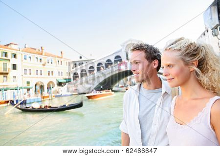Venice couple by Rialto Bridge on Grand Canal on travel together. Young happy couple on holidays or honeymoon having cute romantic vacation in Italy by Grand Canal on Rialto Bridge
