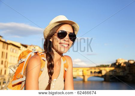 Backpacking women traveler on travel in Florence wearing sunglasses smiling happy by Ponte Vecchio during vacation holidays in Tuscany, Italy, Europe.