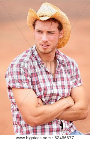 Cowboy man handsome and good looking with hat in rural USA countryside. Male model in american western prairie landscape nature on ranch or farm in USA.